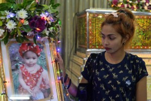 Jiranuch Trirat, mother of 11-month-old daughter who was killed by her father who broadcast the murder on Facebook, stands next to a picture of her daughter at a temple in Phuket, Thailand April 25, 2017. REUTERS/Sooppharoek Teepapan