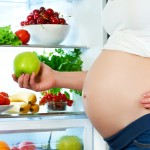 nutrition and diet during pregnancy. Pregnant woman standing near refrigerator with fruits and vegetables