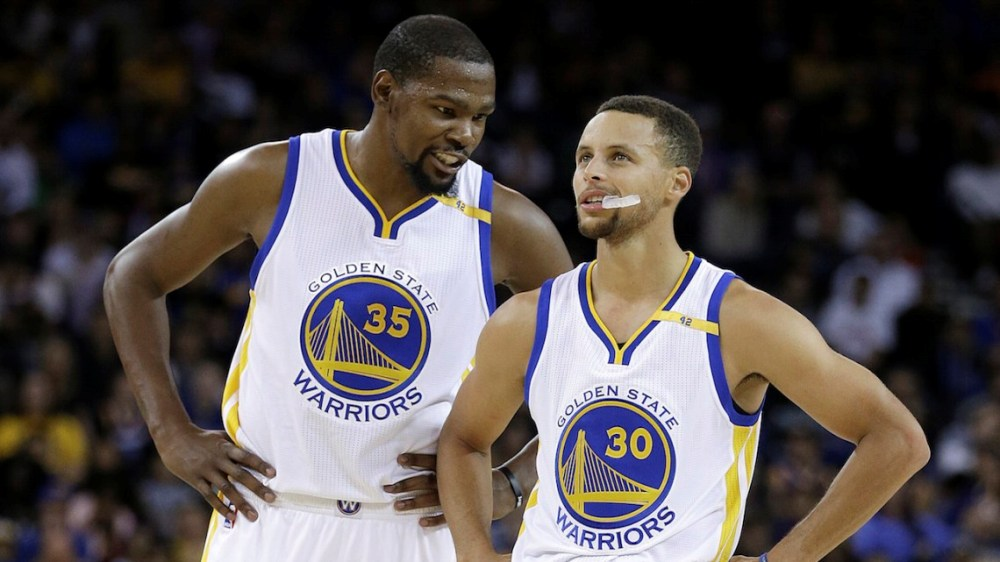 Golden State Warriors' Kevin Durant, left, speaks with Stephen Curry (30) during the first half of a pre-season NBA basketball game against the Los Angeles Clippers on Tuesday, Oct. 4, 2016, in Oakland, Calif. (AP Photo/Ben Margot)